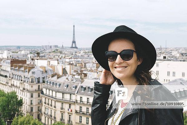 Frankreich  Paris  Porträt einer glücklichen Frau am Aussichtspunkt mit schwarzem Hut und Sonnenbrille