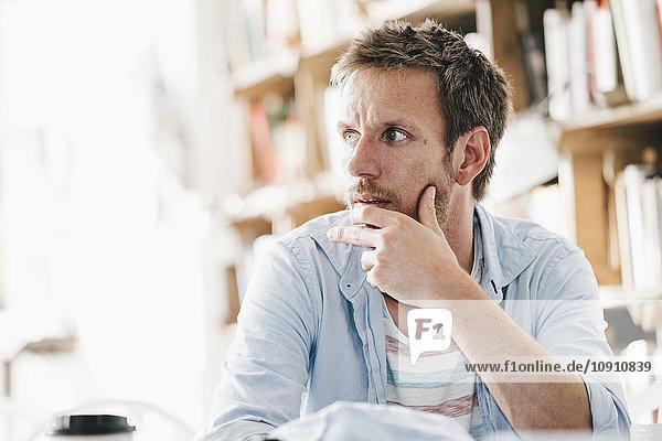 Junger Mann sitzt im Café
