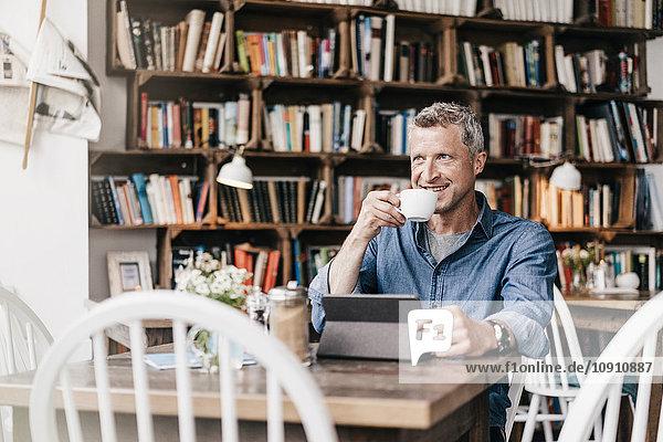 Erwachsener Mann sitzt im Café mit digitaler Tablette und trinkt Kaffee.