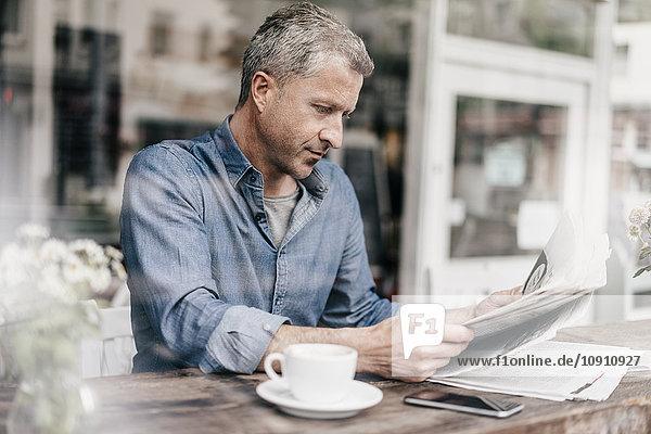 Erwachsener Mann sitzt im Café und liest Zeitung.