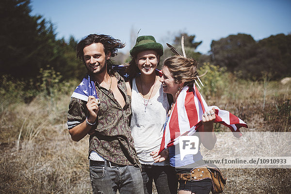 Three hippies with US flag in the nature