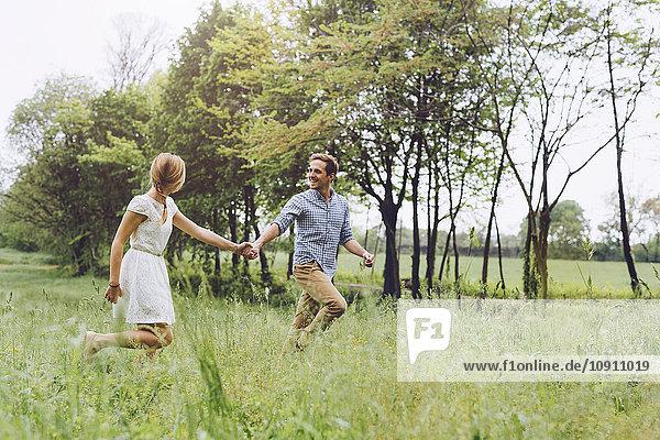 Verliebtes Paar beim Laufen auf einer Wiese Händchen haltend