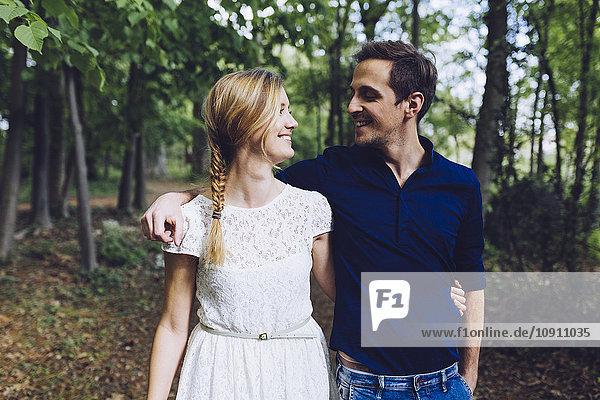 Verliebtes Paar geht Arm in Arm im Wald spazieren