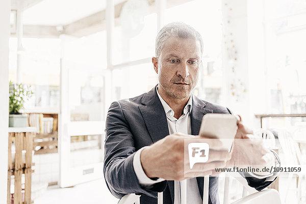Geschäftsmann im Cafe mit Smartphone