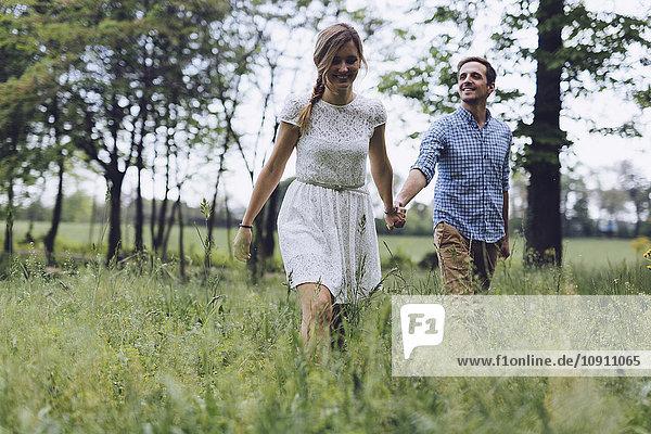 Verliebtes Paar hält sich beim Spaziergang auf einer Wiese an den Händen.