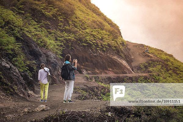 Indonesien  Java  Zwei Frauen beim Bergwandern und Fotografieren