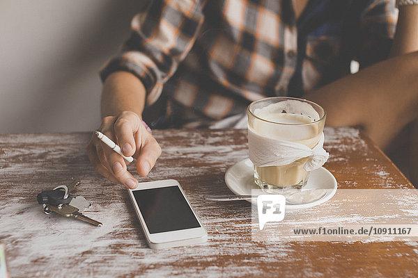 Frau mit Handy im Café