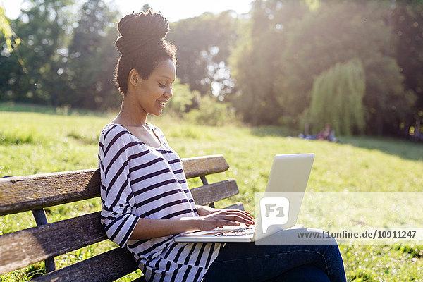 Junge Frau sitzt auf der Parkbank mit Laptop