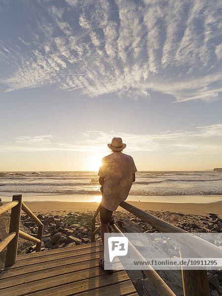 Portugal  älterer Mann auf einem Geländer am Strand sitzend