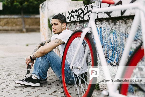 Junger Mann sitzt an der Graffiti-Wand