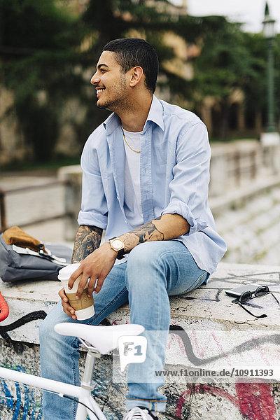 Lächelnder junger Mann auf Graffiti-Wand sitzend