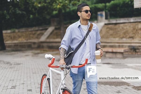 Junger Mann zu Fuß mit dem Fahrrad in der Stadt