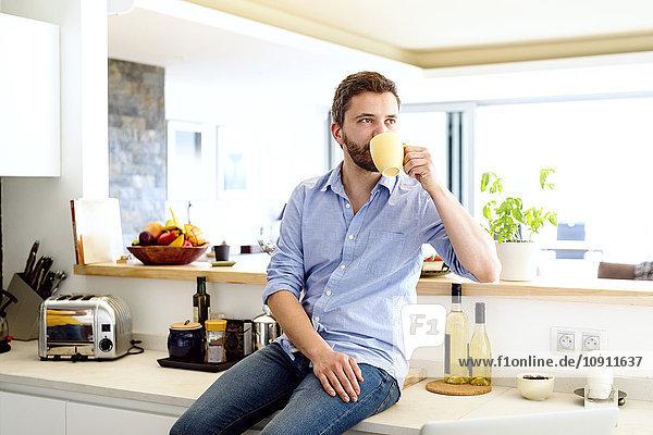 Mann sitzt in der Küche und trinkt Kaffee