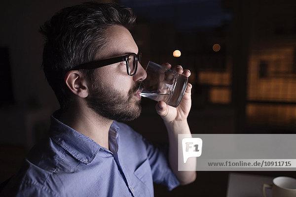Man working at night  drinking water