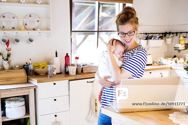 Glückliche Mutter mit Baby in der Küche mit Blick auf Laptop