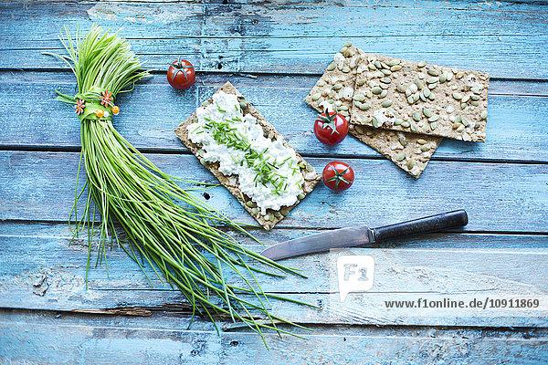 Knäckebrot  Frischkäse  Schnittlauch  Cocktailtomaten und Messer auf Türkisholz
