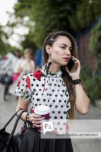 Portrait einer jungen Frau mit Kaffee zum Telefonieren mit Smartphone