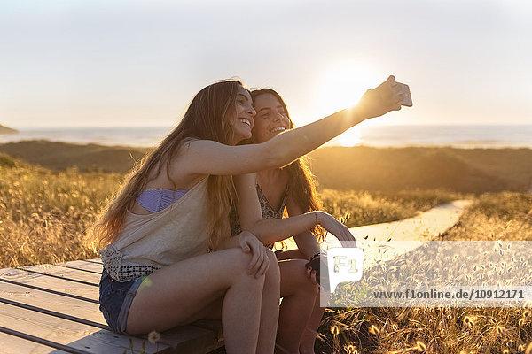 Junge Frauen  die sich bei Sonnenuntergang an den Strand setzen
