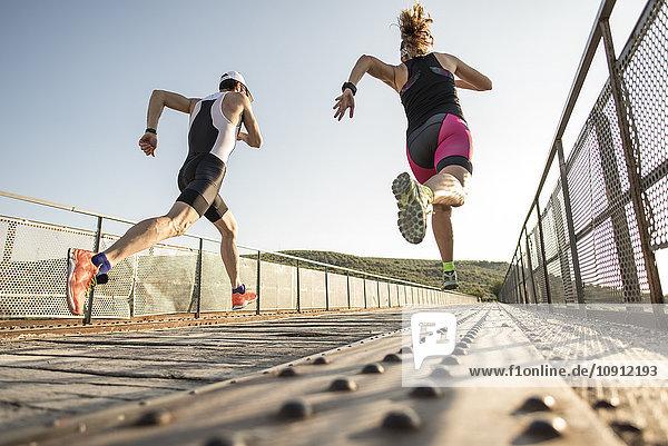 Zwei Athleten laufen auf einer Brücke