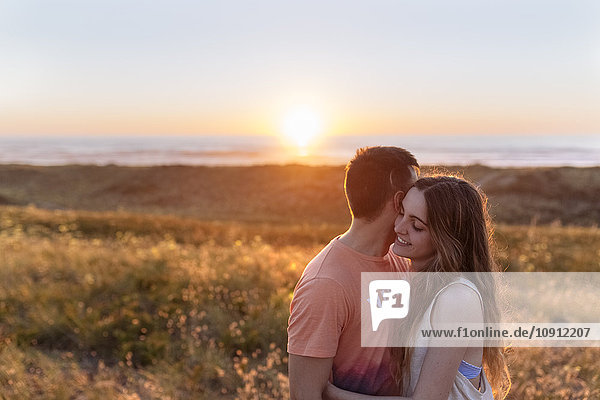 Romantisches junges Paar am Strand bei Sonnenuntergang