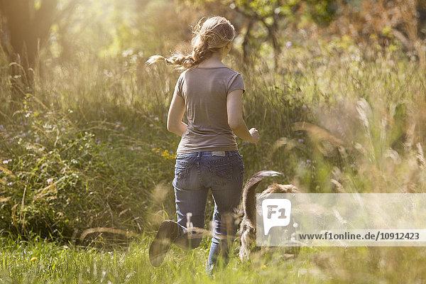 Rückansicht einer jungen Frau  die ihrem Hund auf einer Wiese hinterherläuft.