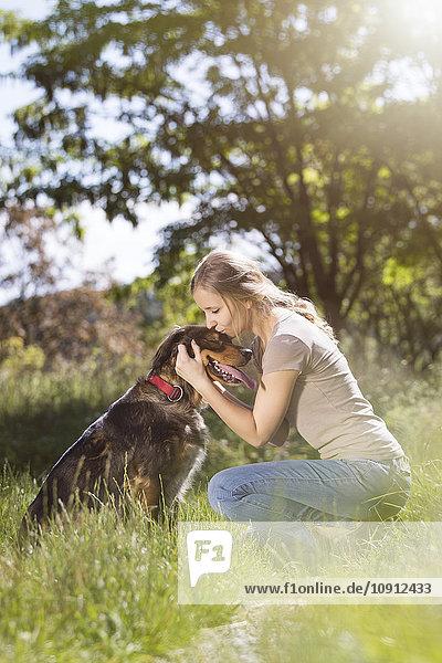 Junge Frau küsst ihren Mischling auf einer Wiese