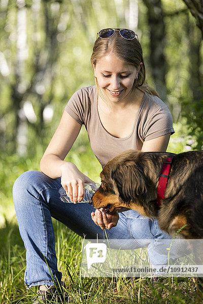 Junge Frau gibt ihrem Hund Wasser