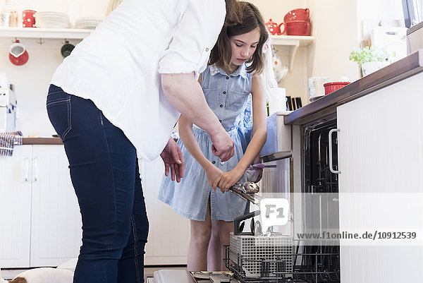 Mother and two girls clearing the dishwasher