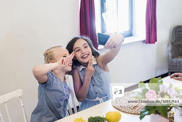 Zwei Mädchen  die einen Selfie bei Tisch nehmen.