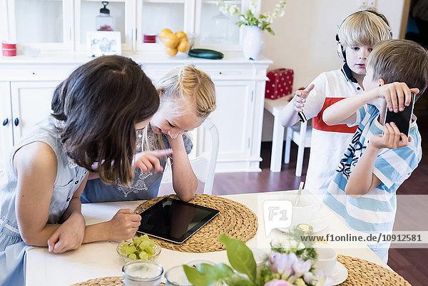 Kinder teilen sich mobile Geräte