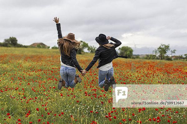 Zwei Frauen springen  Mohnfeld  Hand haltend