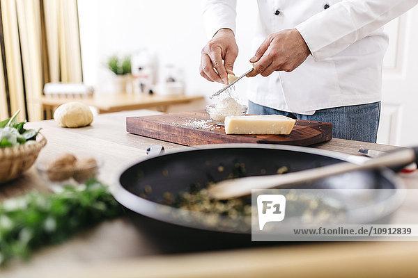 Chef preparing stuffing for ravioli  grating parmesan cheese
