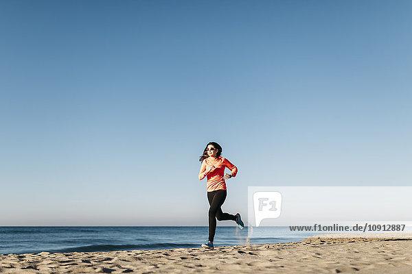 Frau beim Joggen am Strand am frühen Morgen