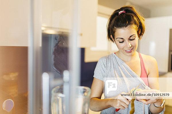 Junge Frau in der Küche  die eine Kiwi schält.