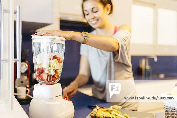 Junge Frau in der Küche bei der Zubereitung eines gesunden Getränks im Mixer