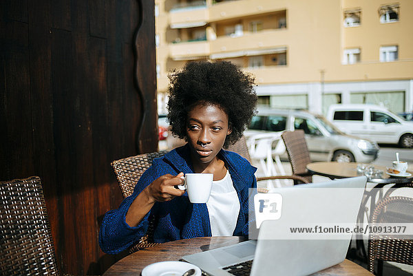 Junge Frau mit Laptop in einem Straßencafé beim Kaffeetrinken