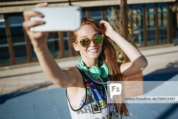 Lächelnde junge Frau mit verspiegelter Sonnenbrille nimmt Selfie mit Smartphone