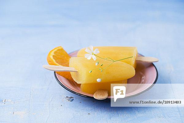 Schale mit hausgemachten orangefarbenen Eis am Stiel Schale mit hausgemachten orangefarbenen Eis am Stiel