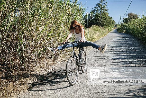Verspielte junge Frau beim Radfahren auf dem Landweg