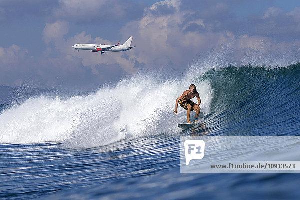 Indonesien  Bali  Surfer auf Welle  Flugzeug im Hintergrund