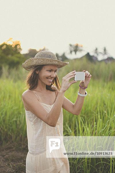 Lächelnde Frau beim Fotografieren mit dem Smartphone in der Natur