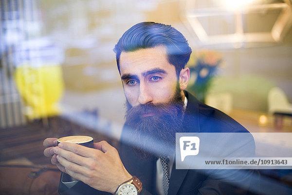 Modischer Mann mit Bart im Café sitzend  Kaffee trinkend