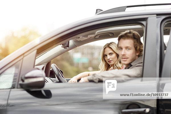 Porträt einer jungen Frau auf dem Beifahrersitz eines Autos
