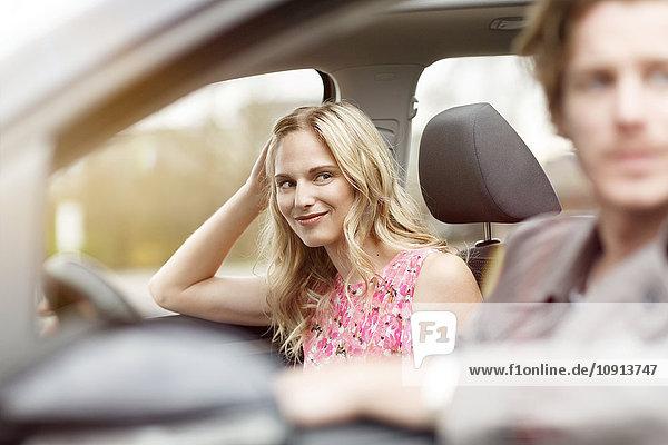 Porträt einer lächelnden blonden Frau auf dem Beifahrersitz im Auto