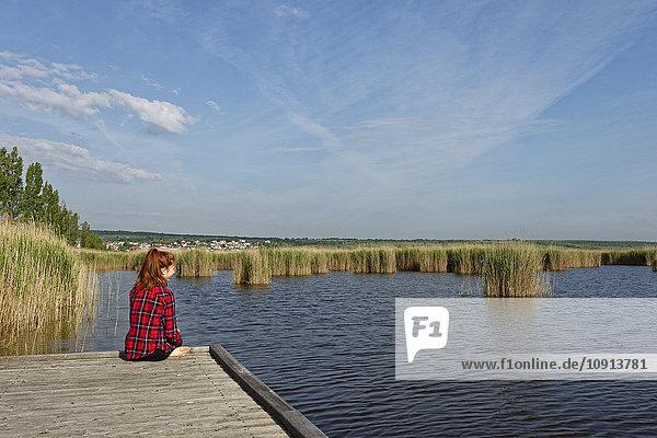Österreich  Burgenland  Neusiedler See  Moerbisch  junges Mädchen am Steg sitzend