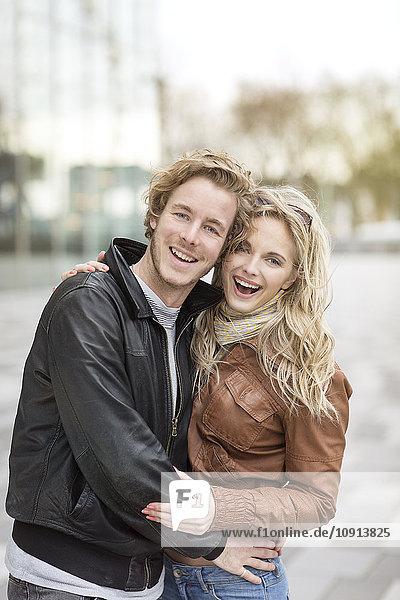 Lachendes junges Paar  das sich in der Stadt umarmt