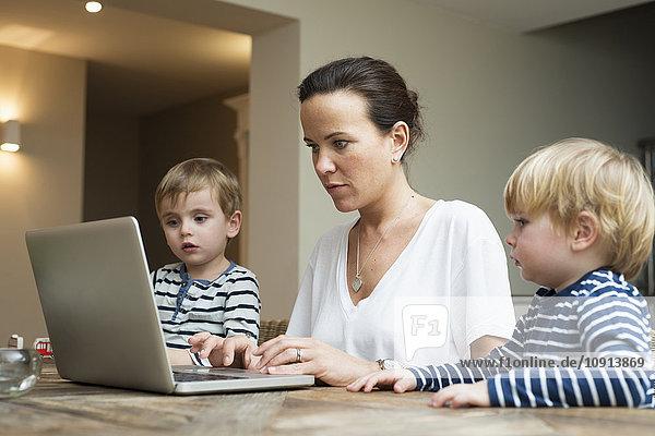 Mutter mit Laptop und ihren Söhnen  die neben ihr sitzen.