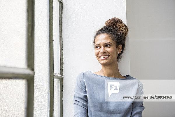 Junge Frau auf Fensterbank sitzend  lächelnd