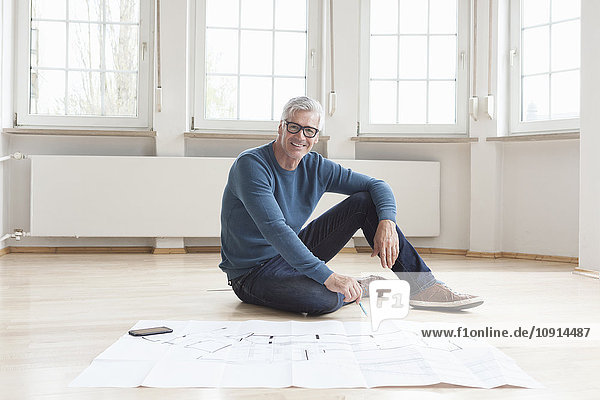 Portrait of smiling man with construction plan in empty apartment