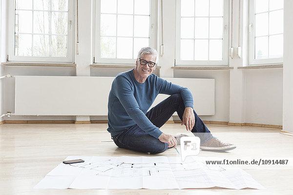 Porträt eines lächelnden Mannes mit Bauplan in leerer Wohnung